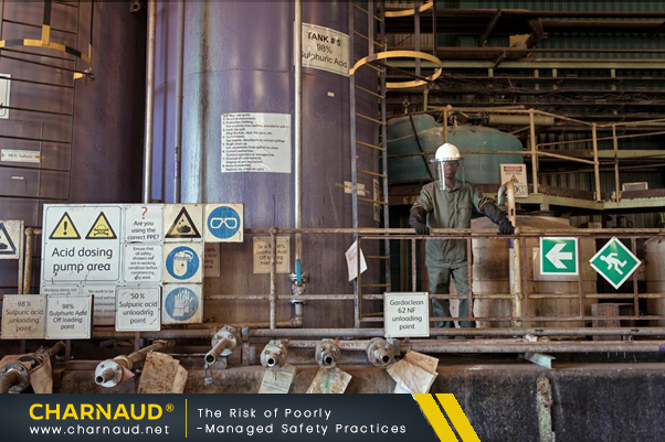 an industrial site featuring large vats, a catwalk, pipes and a worker fully kitted in heavy-duty PPE